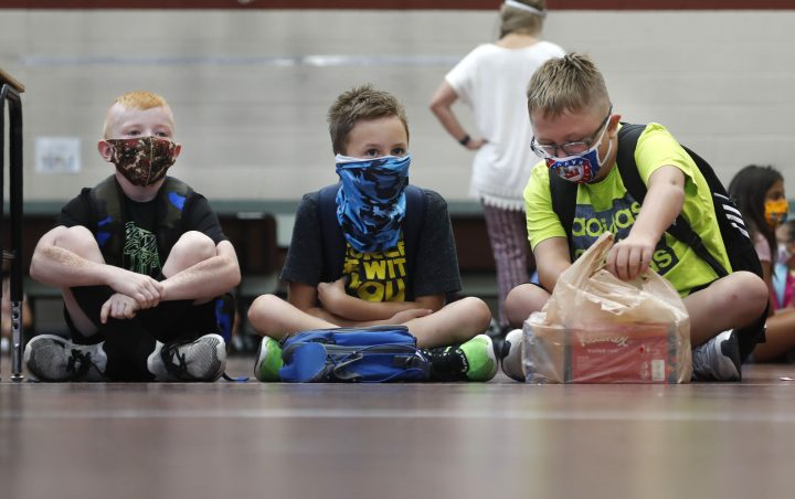 Wearing masks to prevent the spread of COVID19, elementary school students wait for classes to begin in Godley, Texas, Wednesday, Aug. 5, 2020.