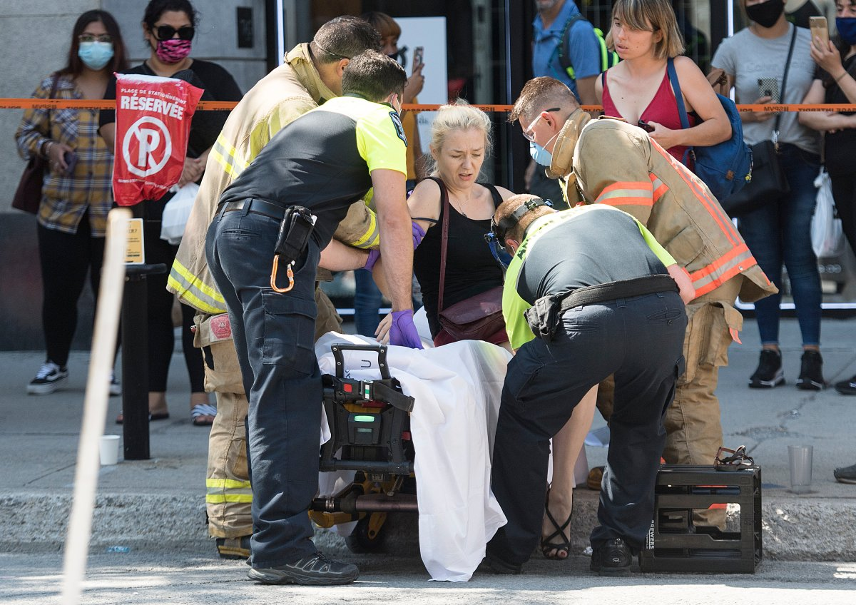 A woman is helped onto a stretcher by paramedics after a jeep sped down a pedestrianized zone on Sainte-Catherine Street in Montreal, Saturday, Aug. 8, 2020.