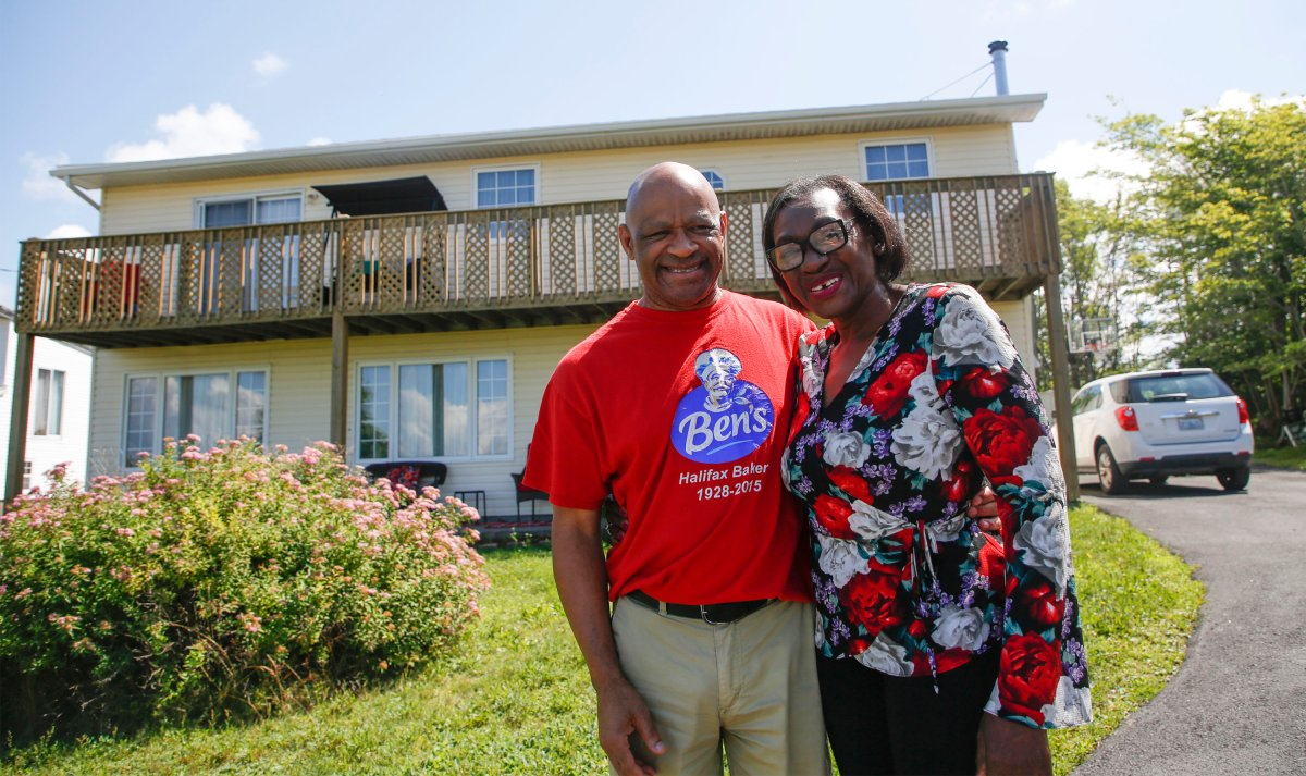 Christopher Downey and his wife Chrissy pose in front of their home in North Preston, N.S., Saturday, August 1, 2020. Christopher Downey finished building his home in 2002 on a parcel of land in North Preston, N.S., that has been in his family for generations. But it was only in late July that Downey says he found out the province intends to issue him a certificate of claim to the land upon which his house was built, the first step in his years-long fight for title.