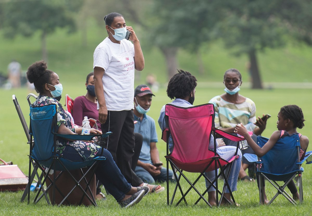 People wear face masks as they gather in a city park in Montreal, Sunday, August 9, 2020, as the COVID-19 pandemic continues in Canada and around the world.