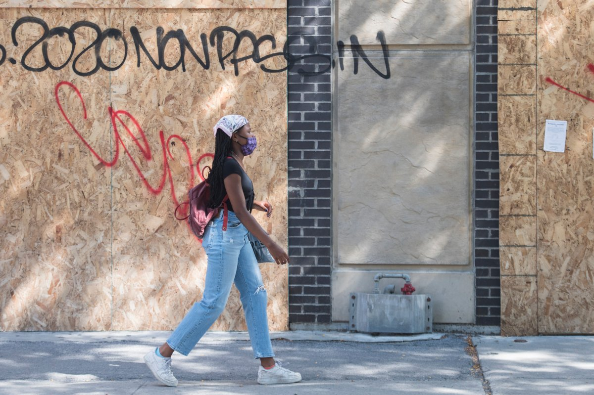 A woman wears a face mask as she walks by a boarded-up storefront on a street in Montreal, Saturday, Aug. 1, 2020, as the COVID-19 pandemic continues in Canada and around the world.