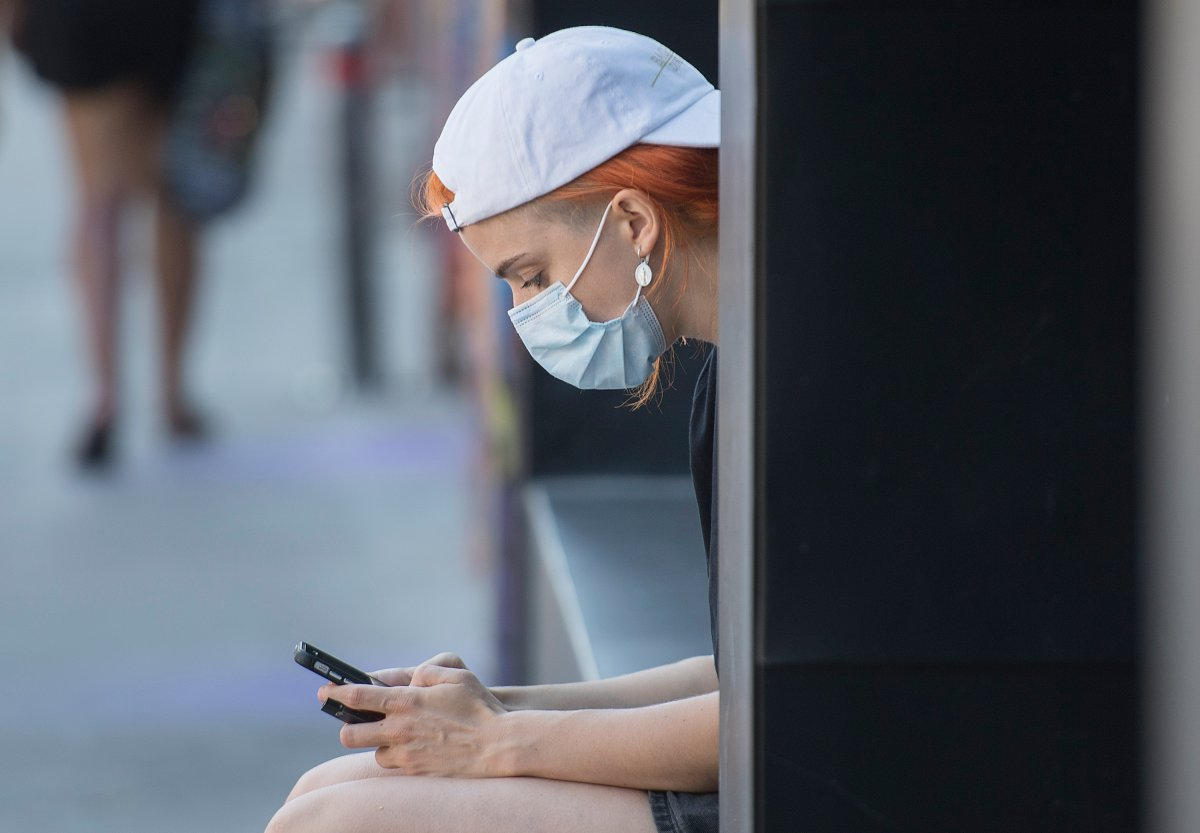 A woman wears a face mask as she browses on her phone in Montreal, Sunday, August 16, 2020, as the COVID-19 pandemic continues in Canada and around the world.