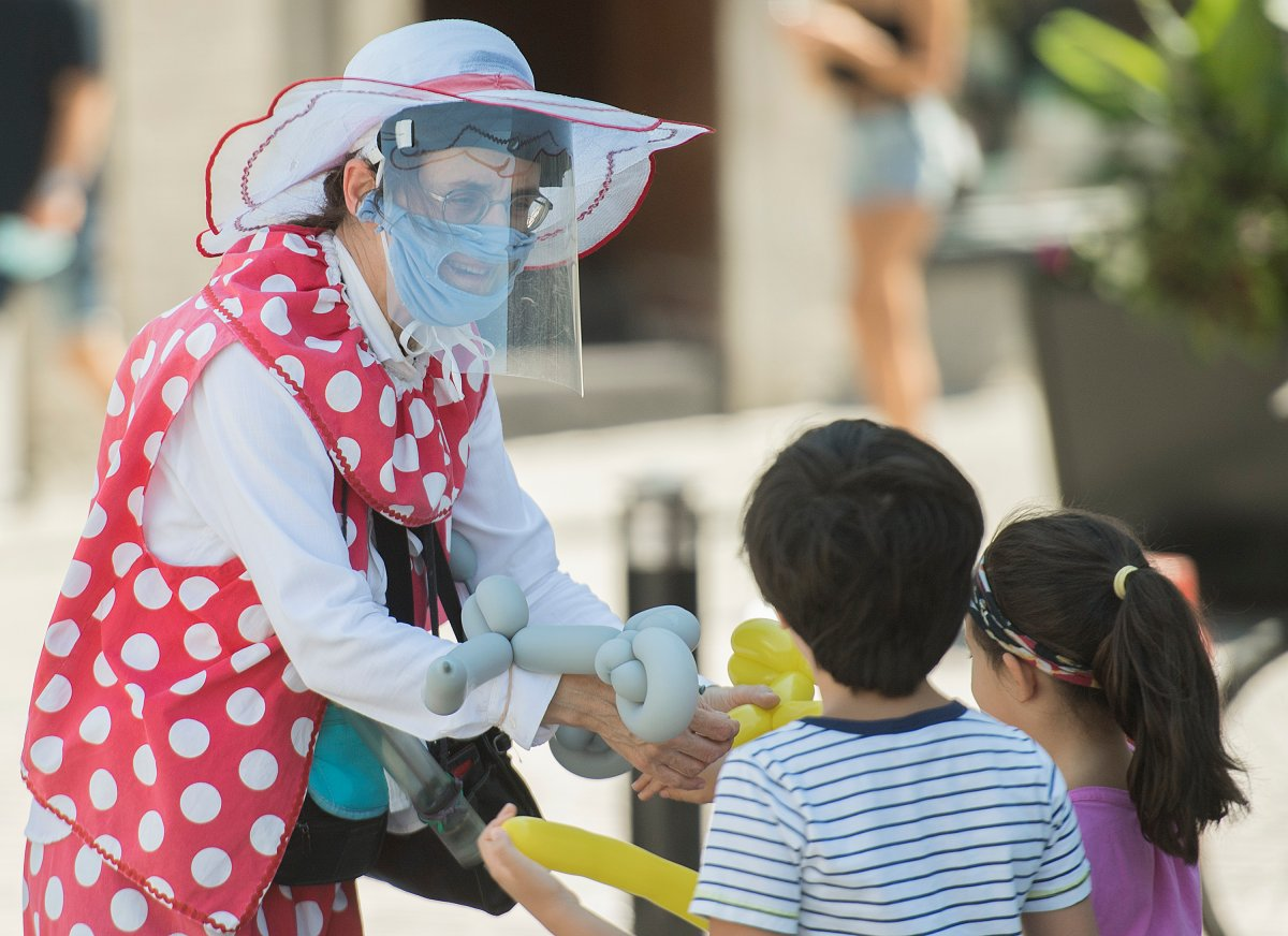 A clown makes balloon-shaped animals for children in the Old Port of Montreal, Sunday, Aug. 16, 2020, as the COVID-19 pandemic continues in Canada and around the world.