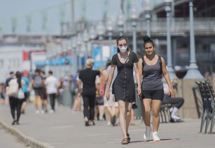A woman wears a face mask as she walks along the promenade in the Old Port of Montreal, Sunday, Aug. 16, 2020, as the COVID-19 pandemic continues in Canada and around the world.