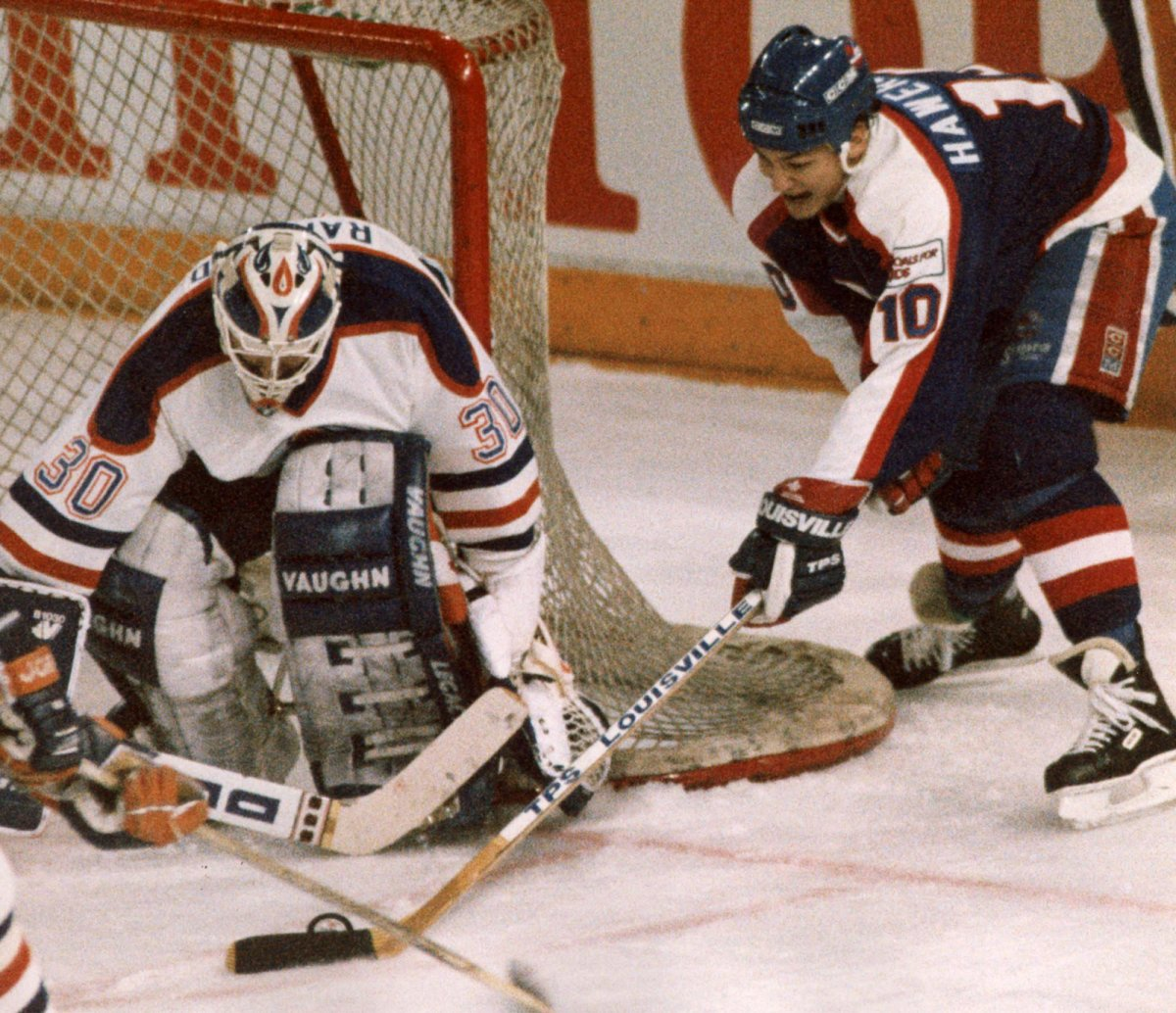The Winnipeg Jets' Dale Hawerchuk tries a wraparound move on the Edmonton Oilers' Bill Ranford during NHL action in Edmonton on April 4, 1990.