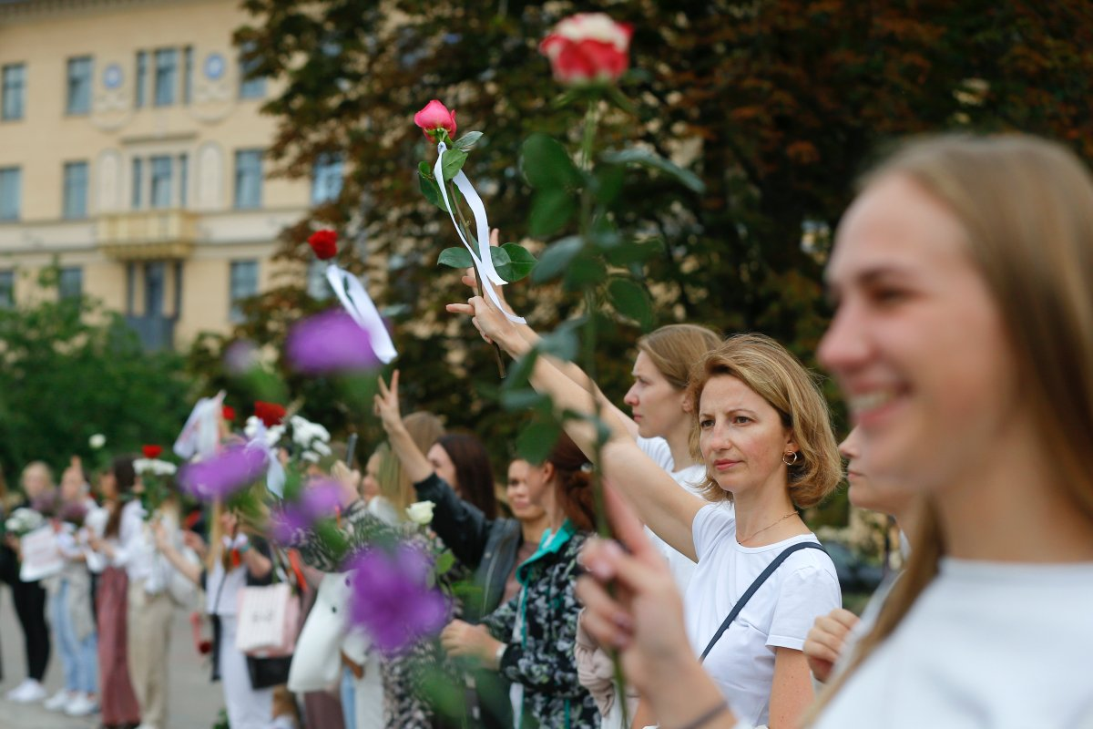 Belarusian opposition supporters hold flowers and flash victory signs during a protest in Victory Square in Minsk, Belarus, Thursday, Aug. 20, 2020.