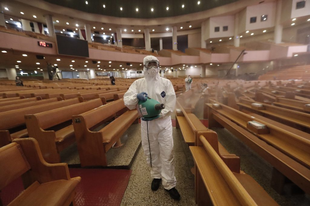 A public official disinfects as a precaution against the coronavirus at the Yoido Full Gospel Church in Seoul, South Korea, Friday, Aug. 21, 2020. South Korea's Centers for Disease Control and Prevention on Friday reported new infections from practically all major cities nationwide, including Busan, Gwangju, Daejeon, Sejong and Daegu, a southeastern city that was the epicenter of a massive outbreak in late February and March.