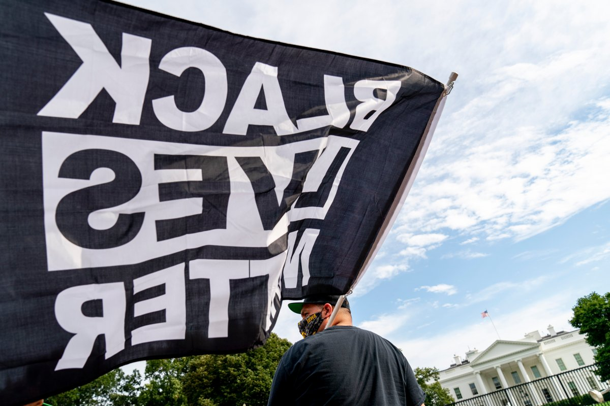 A man carries a Black Lives Matter flag in Lafayette Square outside the White House on the fourth night of the Republican National Convention, Thursday, Aug. 27, 2020, in Washington.