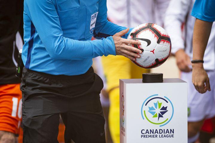 A referee takes the game ball from a pedestal at the beginning of the inaugural soccer match of the Canadian Premier League between Forge FC of Hamilton and York 9 in Hamilton, Ont., Saturday, April 27, 2019.