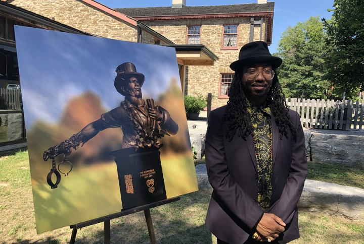 Quentin VerCetty poses beside a picture of his winning proposal for the Joshua Glover memorial.