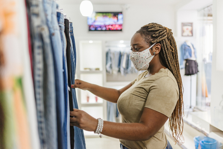 A woman wears a face mask while shopping.