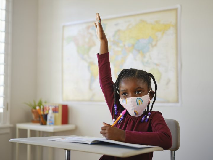 An elementary aged school student in a classroom wearing a mask for protection against infectious disease.