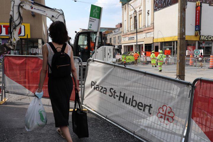 Plaza Saint-Hubert pedestrian walks on temporary pathway while construction continues on St-Hubert Street on Tuesday, Aug. 11, 2020.