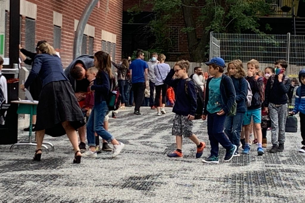 Students line up outside a Montreal school on Aug. 27, 2020. It is the first day back for many children amid the COVID-19 pandemic.