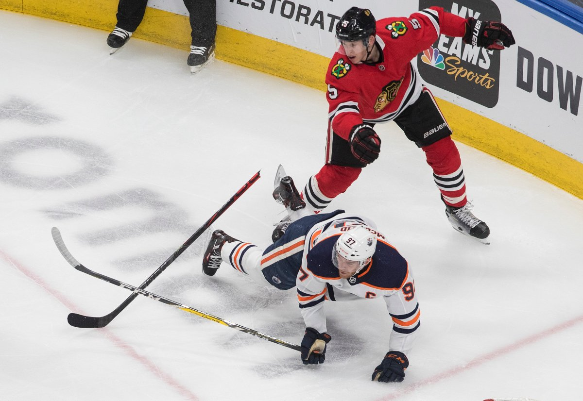 Edmonton Oilers' Connor McDavid (97) is checked by Chicago Blackhawks' Connor Murphy (5) during second period NHL qualifying round game action in Edmonton, on Friday August 7, 2020.