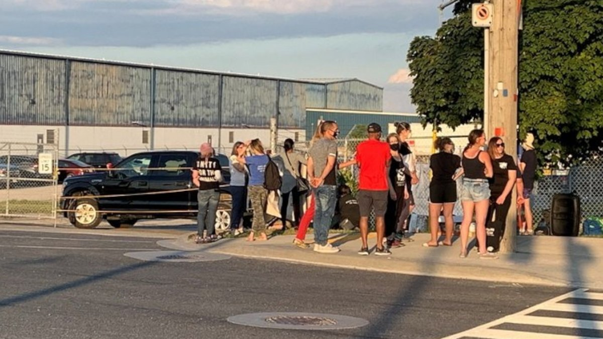 Residents gather outside of the Fearman's pork facility in Burlington Friday June 19, 2020.