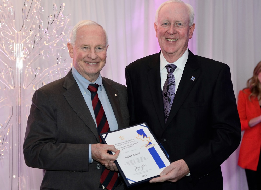 Bill Boland, right, as seen receiving the Caring Canadian Award from then-Governor General David Johnston, left, on March 17, 2013.