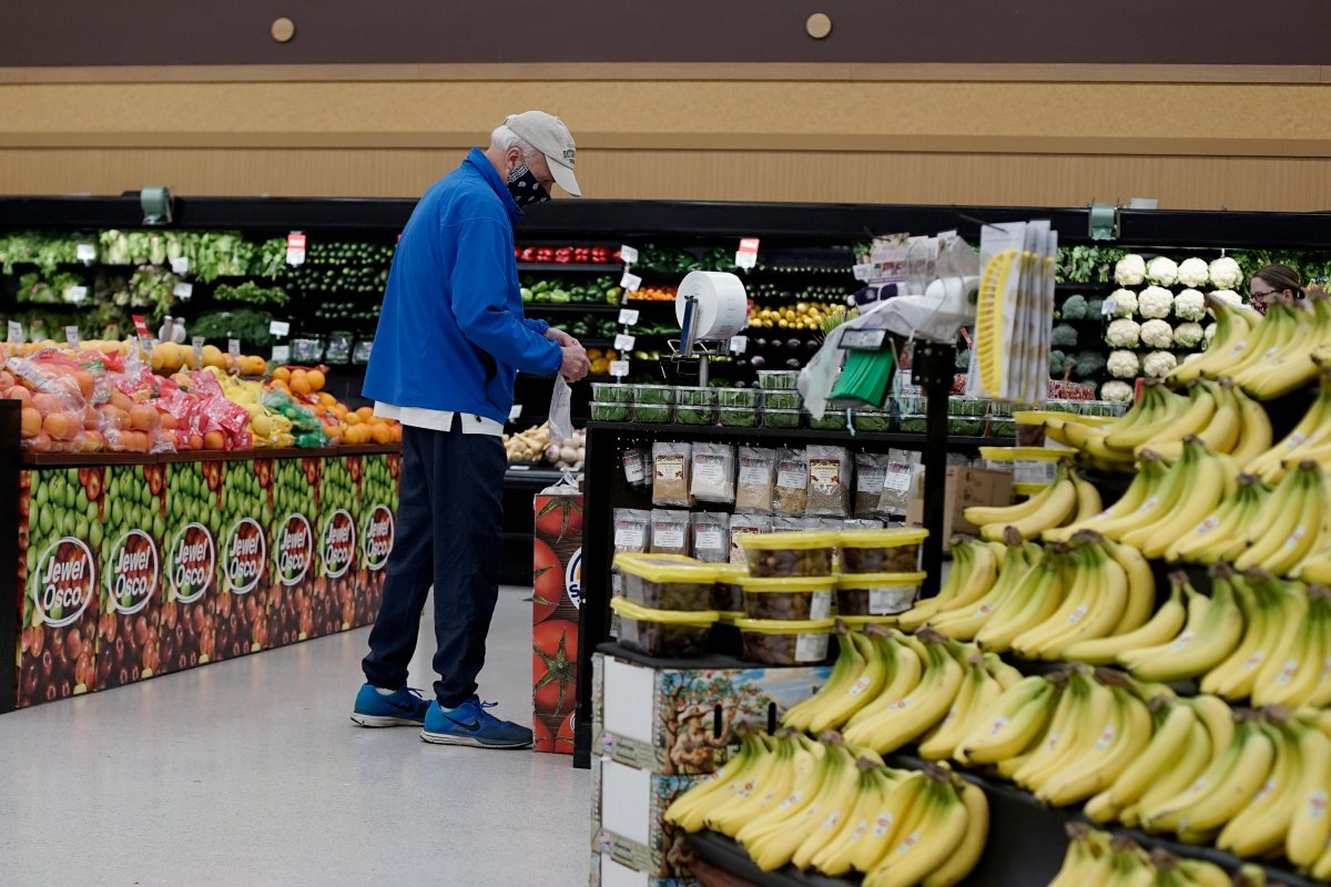 A shopper wears mask and gloves to protect against coronavirus, as he shops at a grocery store in Mount Prospect, Ill., Wednesday, May 13, 2020.