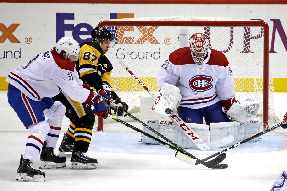 FILE - In this Feb. 14, 2020, file photo, Pittsburgh Penguins' Sidney Crosby (87) can't deflect a shot in front of Montreal Canadiens goaltender Carey Price (31) with Ben Chiarot (8) defending.