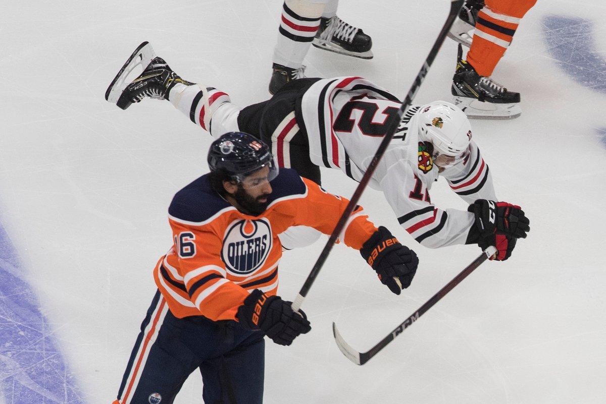 Edmonton Oilers' Jujhar Khaira (16) checks Chicago Blackhawks' Alex DeBrincat (12) during second period NHL playoff action in Edmonton, Saturday, Aug. 1, 2020. THE CANADIAN PRESS/Jason Franson.