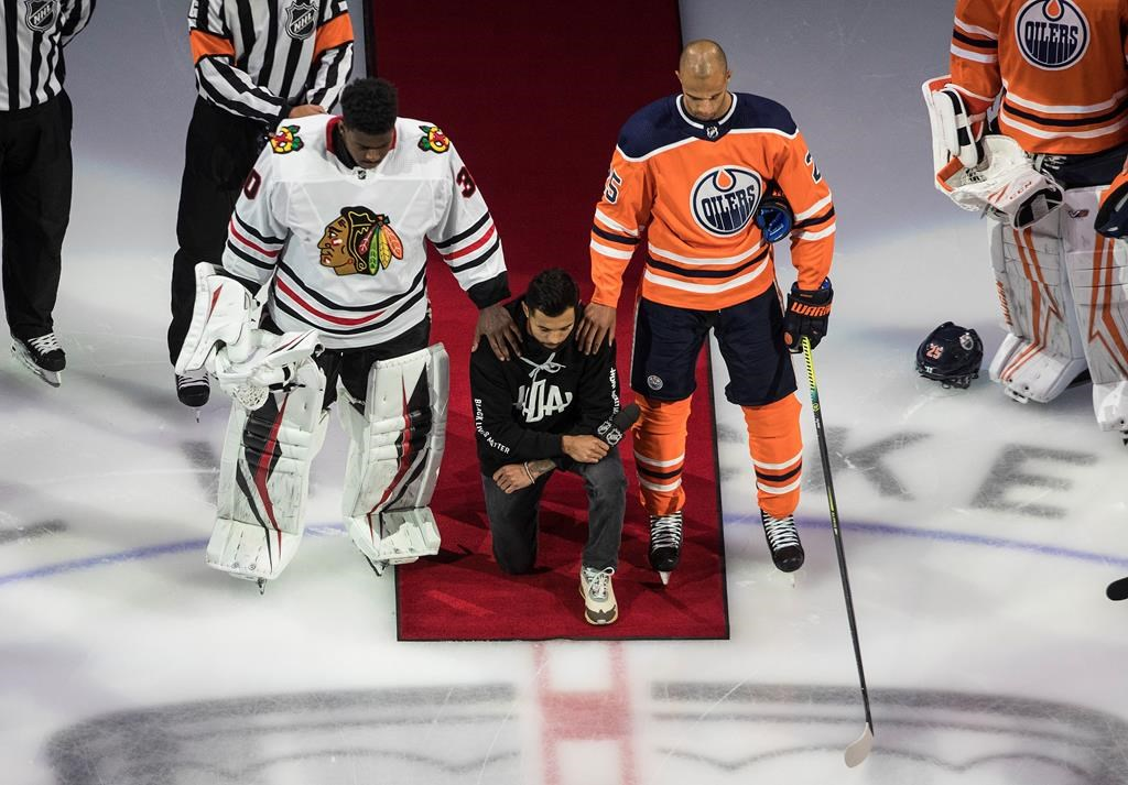 The Minnesota Wild's Matt Dumba takes a knee during the national anthem flanked by the Edmonton Oilers' Darnell Nurse, right, and the Chicago Blackhawks' Malcolm Subban before an NHL playoff game in Edmonton, Saturday, Aug. 1, 2020. THE CANADIAN PRESS/Jason Franson.