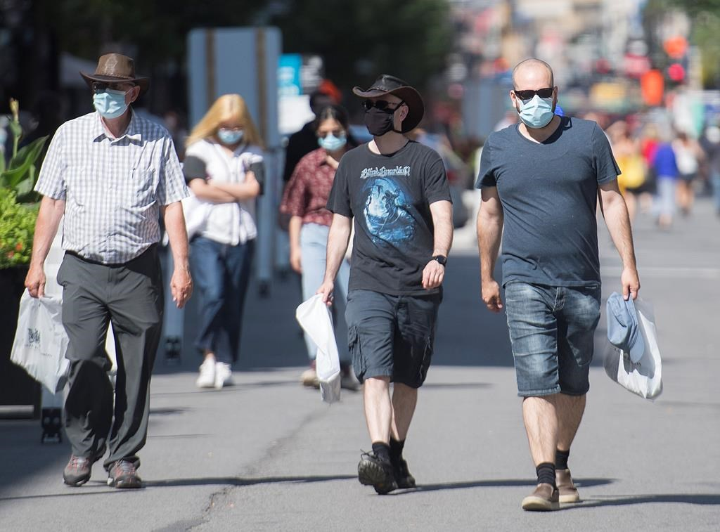 People wear face masks as they walk along Sainte Catherine Street in Montreal, Saturday, Aug. 1, 2020. THE CANADIAN PRESS/Graham Hughes.