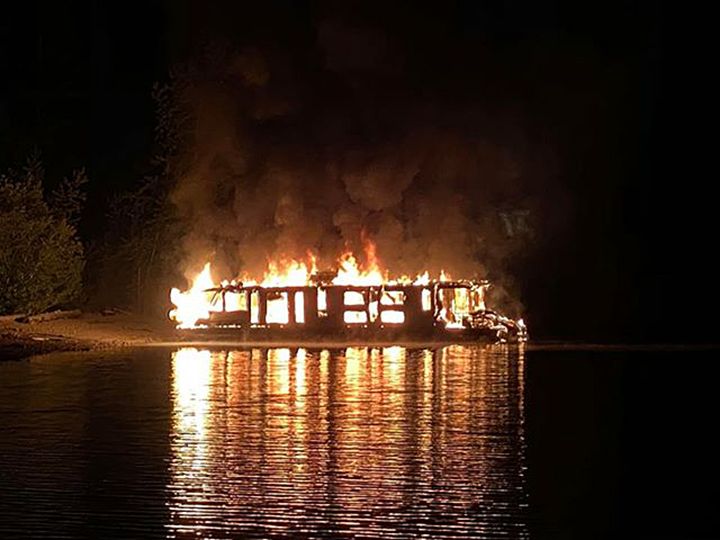 Flames tear through a houseboat on Mara Lake early Tuesday. A witness said the 21 people aboard the houseboat escaped safely.