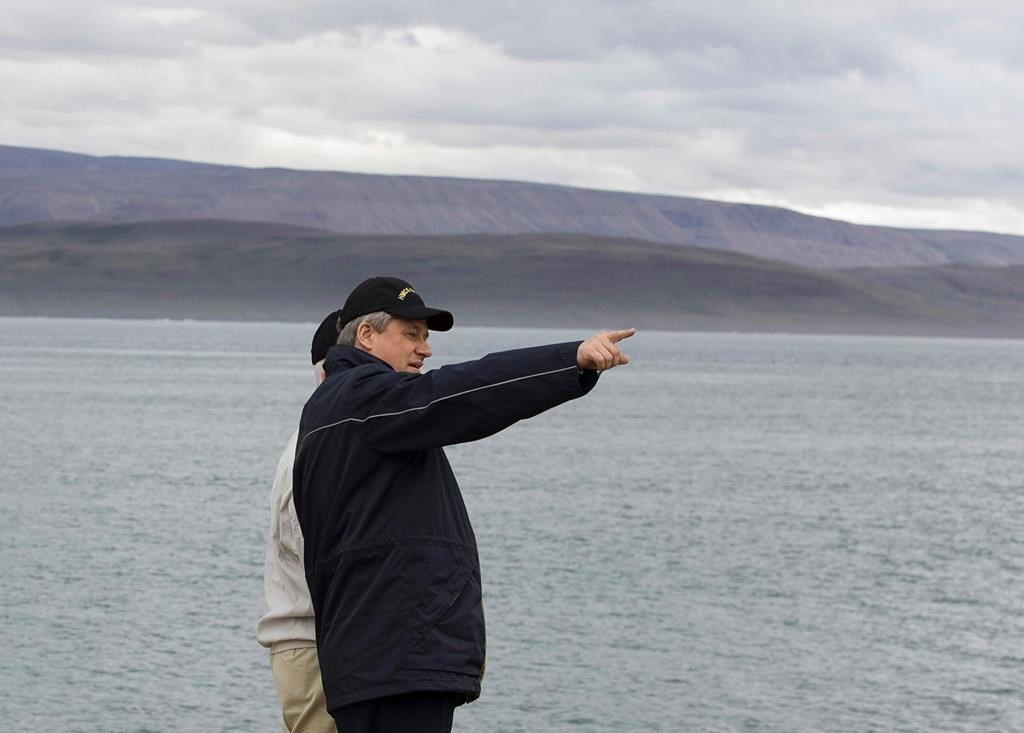 Prime Minister Stephen Harper looks down the shoreline in the Arctic port of Nanisivik, Nunavut on August 10, 2007. The construction of a new military refuelling station in the Arctic is facing yet another delay more than 13 years after it was first promised by the federal government.