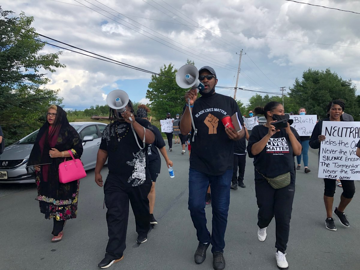 Community organizers Steven Benton (centre) and Marcus Owen (left) lead a Black Lives Matter march through North Preston, N.S. on Aug. 1, 2020.