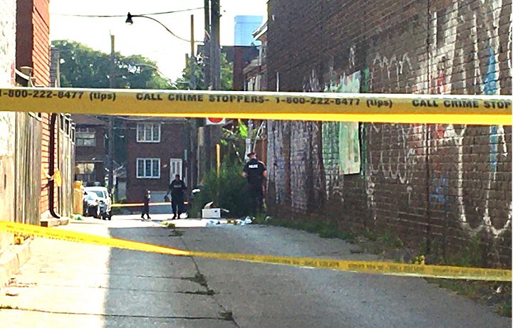 Officers collect evidence in a laneway in the area of Ossington Avenue and Dundas Street Sunday morning.
