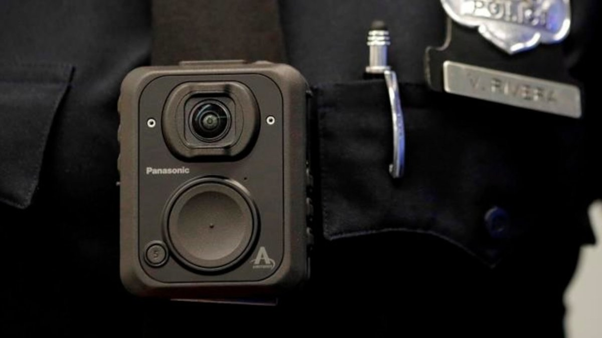 A Newark police officer displays how a body cam is worn during a news conference unveiling new cameras at the Panasonic headquarters in Newark, N.J.