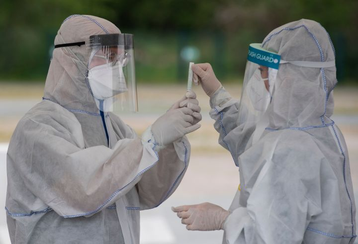 Health professionals wearing protective gear, face shield and face mask label a saliva sample at a drive-in COVID-19 testing facility in Berlin on April 30, 2020, amid the new coronavirus COVID-19 pandemic.
