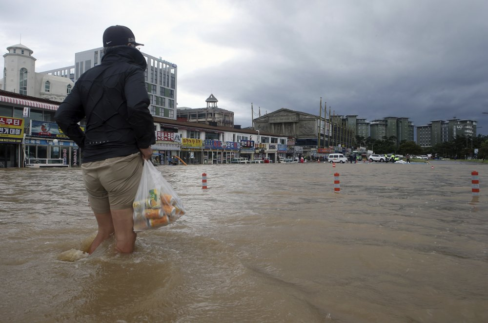A citizen walks through a flooded area in Gangneung, South Korea, Thursday, Sept. 3, 2020. A powerful typhoon ripped through South Korea's southern and eastern coasts with tree-snapping winds and flooding rains Thursday, knocking out power to thousands of homes.
