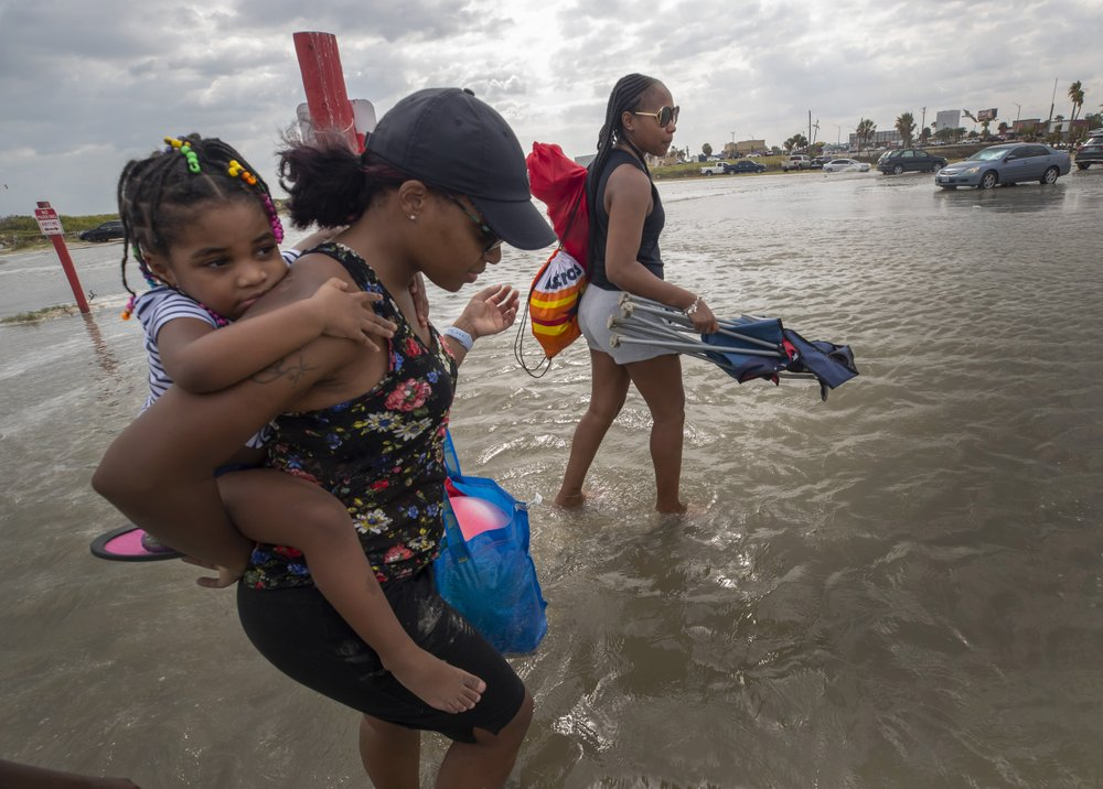 Stacey Young gives her daughter, Kylee Potts, a piggyback ride across the flooding Stewart Beach parking lot in Galveston, Texas on Saturday, Sept. 19, 2020. Tropical Storm Beta continues to move through the Gulf of Mexico and is expected to bring tidal surge and heavy rain to the area.