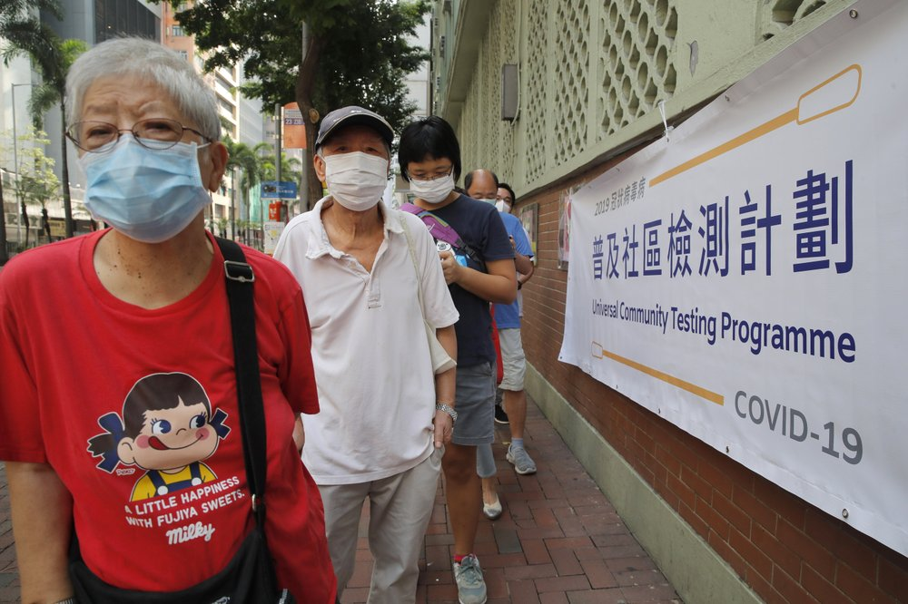 People wearing face masks queue for the coronavirus test outside a testing center in Hong Kong, Tuesday, Sept. 1, 2020. Hong Kong began a voluntary mass-testing program for coronavirus Tuesday as part of a strategy to break the chain of transmission in the city's third outbreak of the disease. The virus-testing program has become a flash point of political debate in Hong Kong, with many distrustful over resources and staff being provided by the China's central government and fears that the residents' DNA could be collected during the exercise.