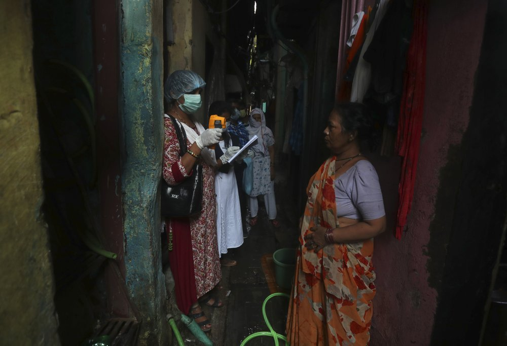 A health worker screens people for symptoms of COVID-19 in Dharavi, one of Asia's biggest slums, in Mumbai, India, Friday, Sept. 4, 2020.The number of people infected with the coronavirus in India rose by another 80,000 and is near Brazil's total, the second-highest in the world.