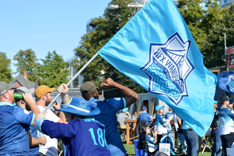 Denton Froese carries a HFX Wanderers FC flag at a fan event to watch the team compete in Prince Edward Island in 2020.