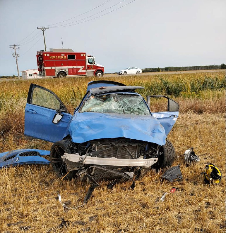 A severely damaged BMW sedan sits in the ditch on Highway 2, east of St. Claude on Monday. RCMP say the driver was racing another vehicle when he lost control.