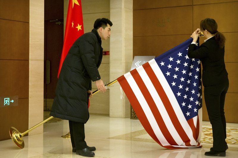 FILE - In this Feb. 14, 2019, file photo, Chinese staffers adjust a U.S. flag before the opening session of trade negotiations between U.S. and Chinese trade representatives at the Diaoyutai State Guesthouse in Beijing. China is delaying the renewal of press cards for at least five journalists working at four U.S. media outlets, an organization of foreign correspondents said Monday, Sept. 7, 2020 making them vulnerable to expulsion in apparent retribution for Washington's targeting of Chinese reporters working in the United States.