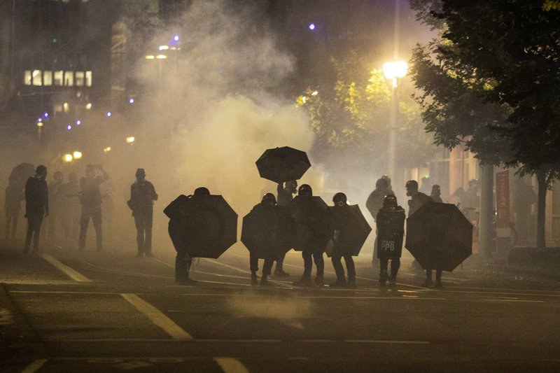 Tear gas fills the air during protests, Friday, Sept. 18, 2020, in Portland, Ore. The protests, which began over the killing of George Floyd, often result frequent clashes between protesters and law enforcement.