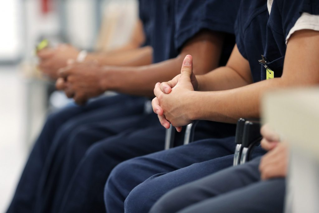 Detainees sit and wait for their turn at the medical clinic at the Winn Correctional Center in Winnfield, La., Thursday, Sept. 26, 2019. Nearly 1,500 migrants are detained at Winn.