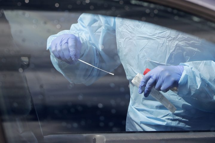 A medical assistant prepares to take a swab from a patient at a drive-thru and walk-up coronavirus testing site in this file photo.