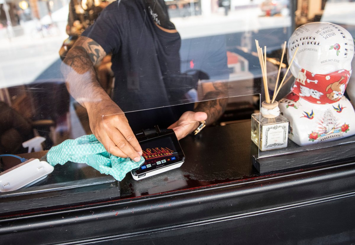 FILE - Owner Ankur Vadhera uses sanitizer on a credit card machine, at Capital Barber Shop in Ottawa, on its first day of reopening as Ontario moves into Stage 2 of its plan to lift lockdowns implemented in response to the COVID-19 pandemic, on Friday, June 12, 2020.