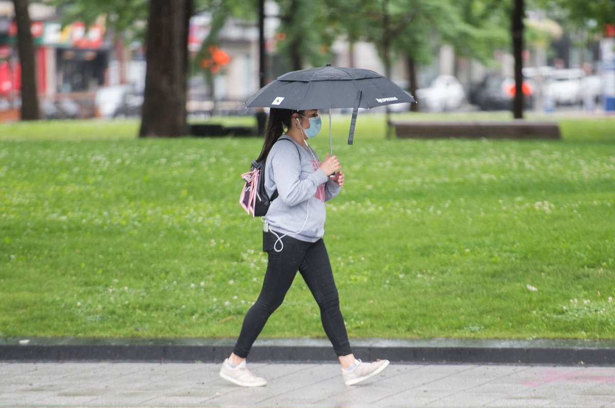 A woman wears a face as she walks along a street in the rain in Montreal, Saturday, July 11, 2020, as the COVID-19 pandemic continues in Canada and around the world.