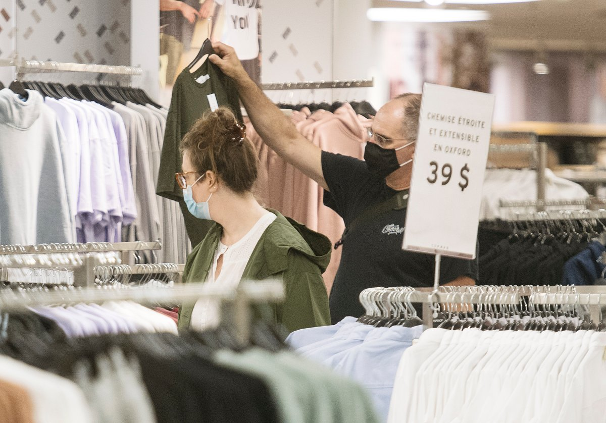 People wear face masks as they shop in a department store in Montreal, Sunday, August 2, 2020, as the COVID-19 pandemic continues in Canada and around the world.