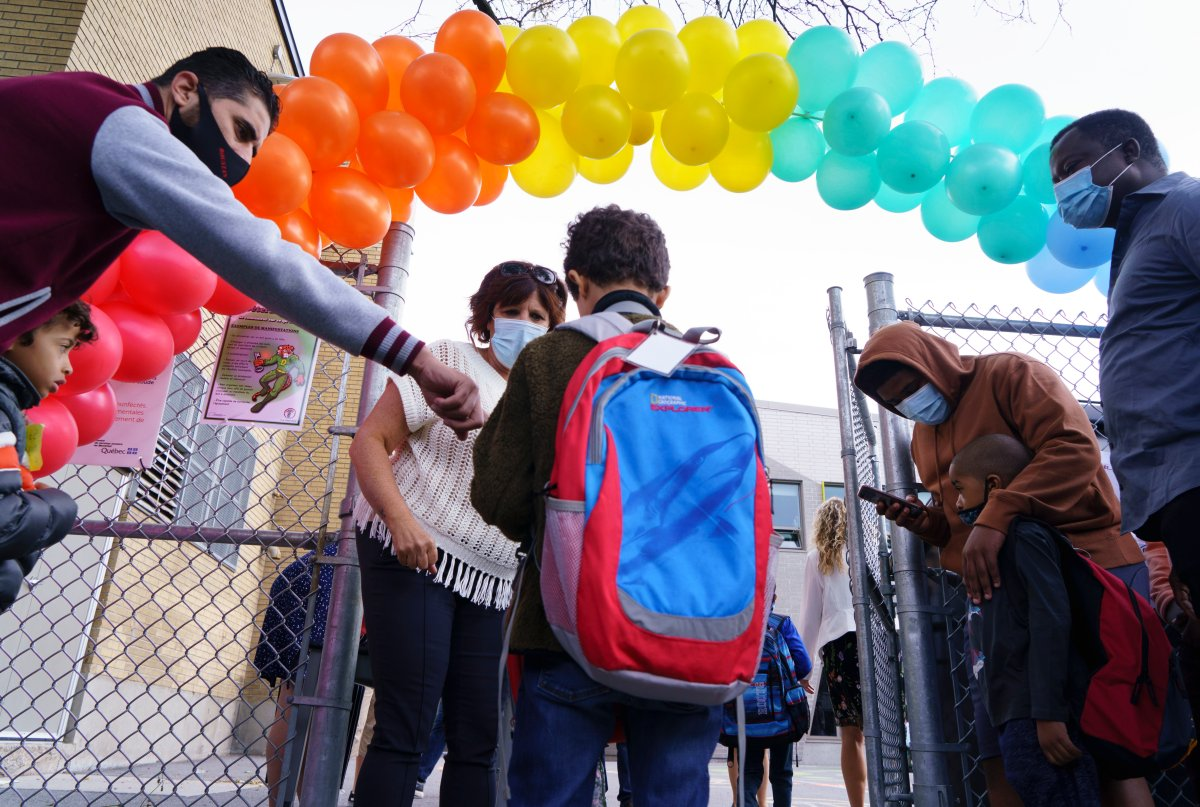 A student is greeted at the Philippe-Labarre Elementary School in Montreal, on Thursday, August 27, 2020. Thousands of Quebec students return to class in the shadow of the COVID-19 pandemic.
