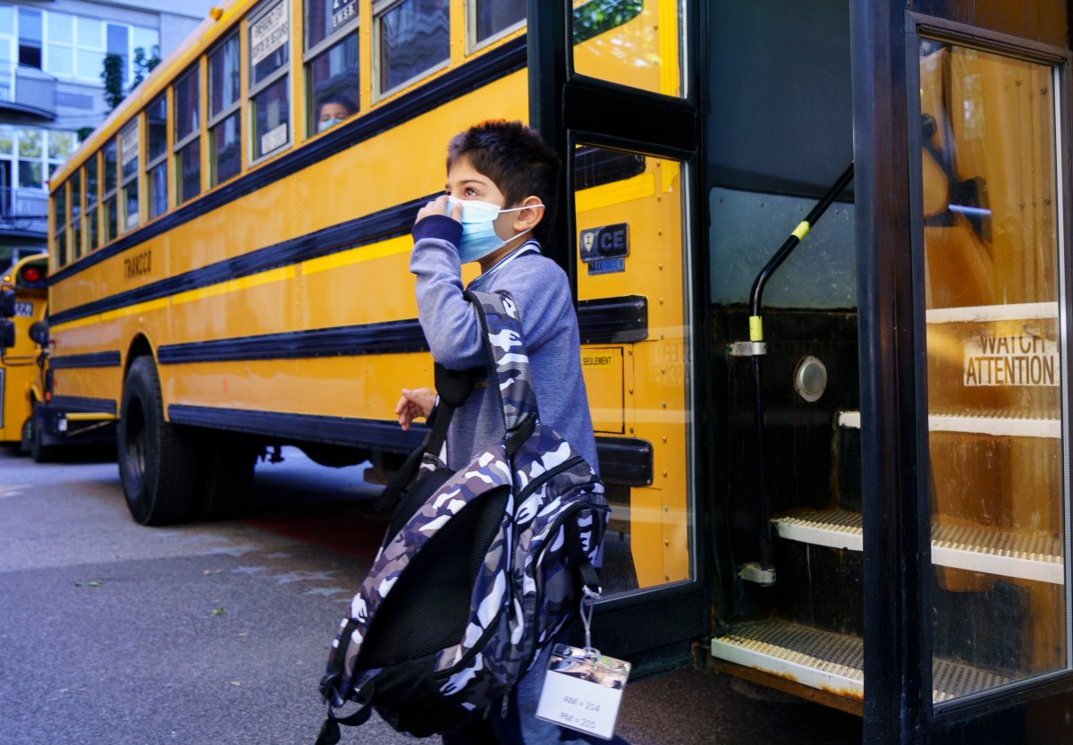 A student adjusts his protective mask as he walks off the bus at the Bancroft Elementary School as students go back to school in Montreal, on Monday, August 31, 2020.