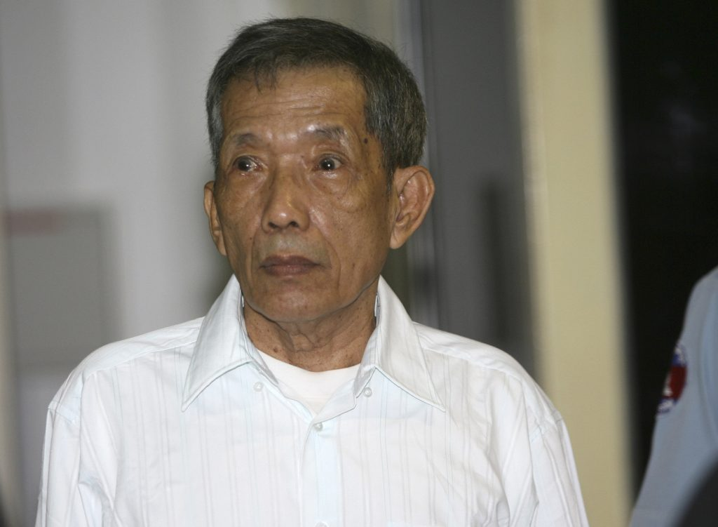 FILE - In this March 30, 2020, file photo, former Khmer Rouge prison chief Kaing Guek Eav, also know as Duch, looks on during the first day of a U.N.-backed tribunal in Phnom Penh, Cambodia. The Khmer Rouge's chief jailer, who admitted overseeing the torture and killings of as many as 16,000 Cambodians while running the regime's most notorious prison, died at a hospital in Cambodia early Wednesday morning, Sept. 2, 2020. Kaing Guek Eav, known as Duch, was 77 and had been serving a life prison term for war crimes and crimes against humanity.