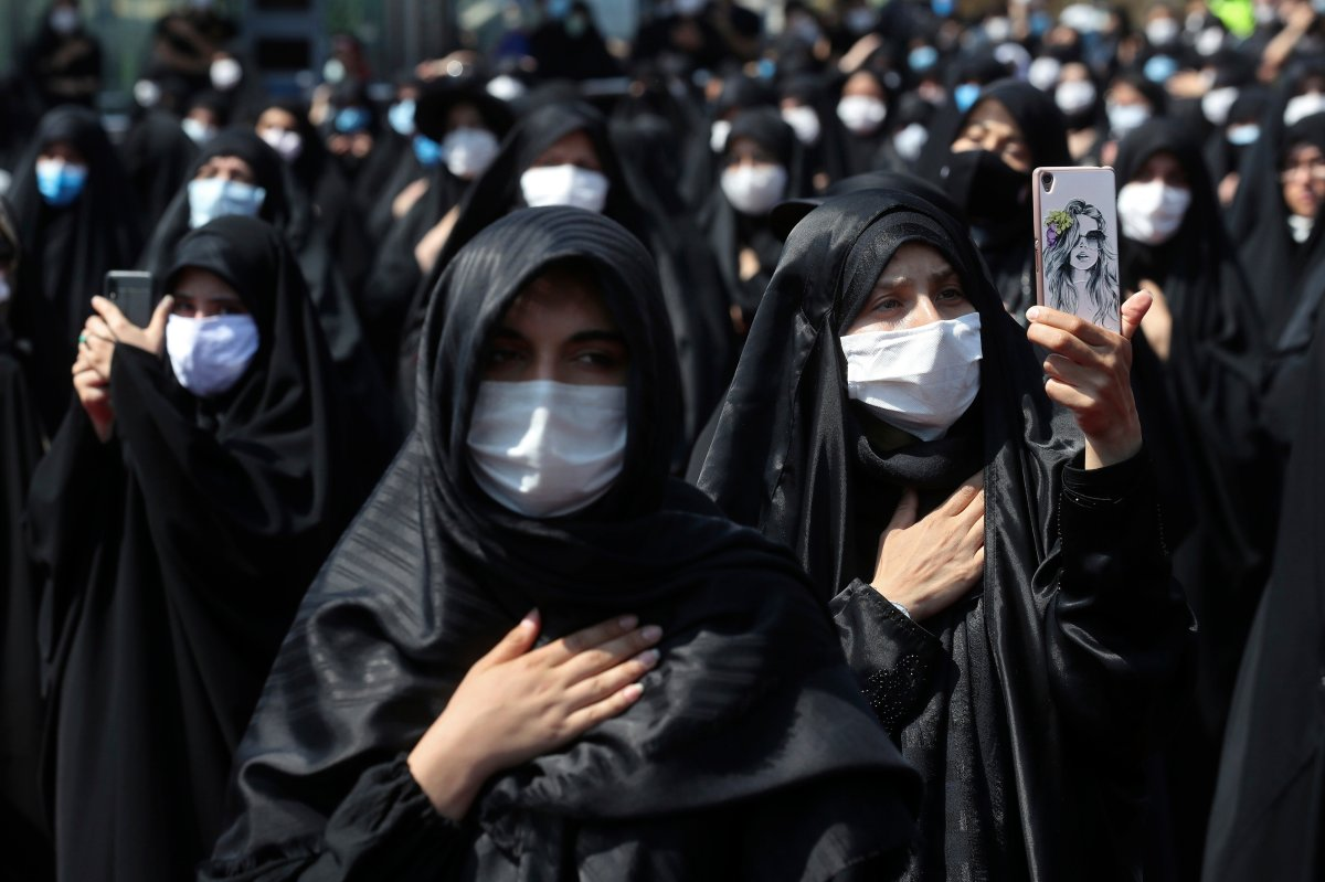 FILE - In this Sunday, Aug. 30, 2020 file photo, people wearing protective face masks to help prevent spread of the coronavirus mourn during an annual ceremony commemorating Ashoura in Tehran, Iran.