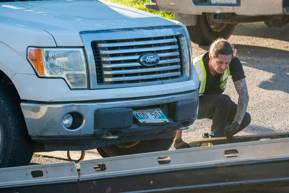 A tow truck operator removes a truck with Manitoba licence plates from the front of a home on Parklane Avenue in Oshawa, Ont. on Friday, September 4, 2020. Durham Regional Police say five people were found dead and another with serious injuries in the home east of Toronto after an early morning shooting. THE CANADIAN PRESS/Frank Gunn.